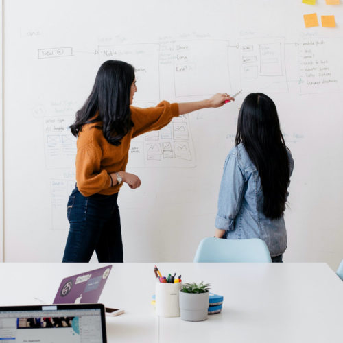 Two women working together at a whiteboard